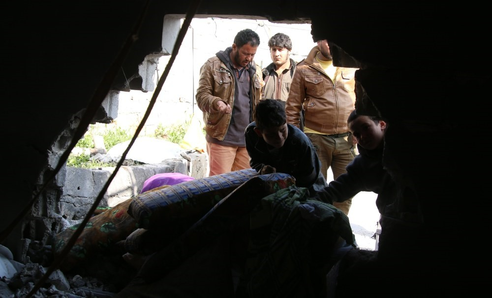 Refugees try to safe their belongings from a makeshift tent that was reportedly damaged by a mortar shell allegedly fired by the YPG in Atma, a town in the northern countryside of Idlib, Syria.