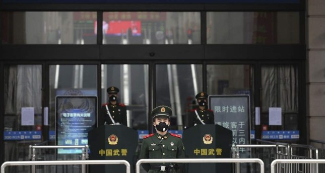 Chinese paramilitary police stand guard outside the closed Hankou Railway Station, Wuhan, Jan. 23, 2020. AP Photo