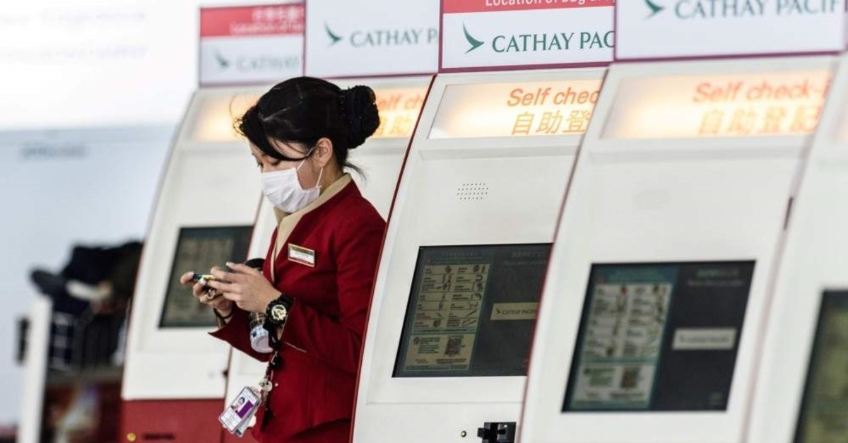 In this file photo, a mask-clad Cathay Pacific employee walks past a row of self check-in counters at the international airport in Hong Kong, March 15, 2017. (AFP Photo)
