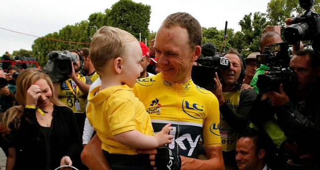 Tour de France winner Britain's Chris Froome holds son Kellan during the twenty-first and last stage of the Tour de France cycling race in Paris, France, Sunday, July 23, 2017. (AP Photo)
