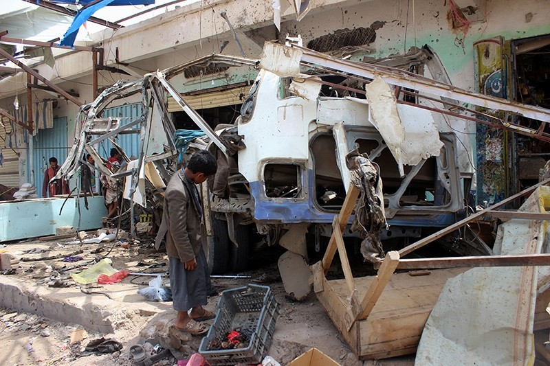 In file photo taken on Aug. 10, 2018, a Yemeni child stands next to the destroyed bus at the site of a Saudi-led coalition air strike, that targeted the Dahyan market the previous day in the Houthi rebels' stronghold province of Saada. (AFP Photo)