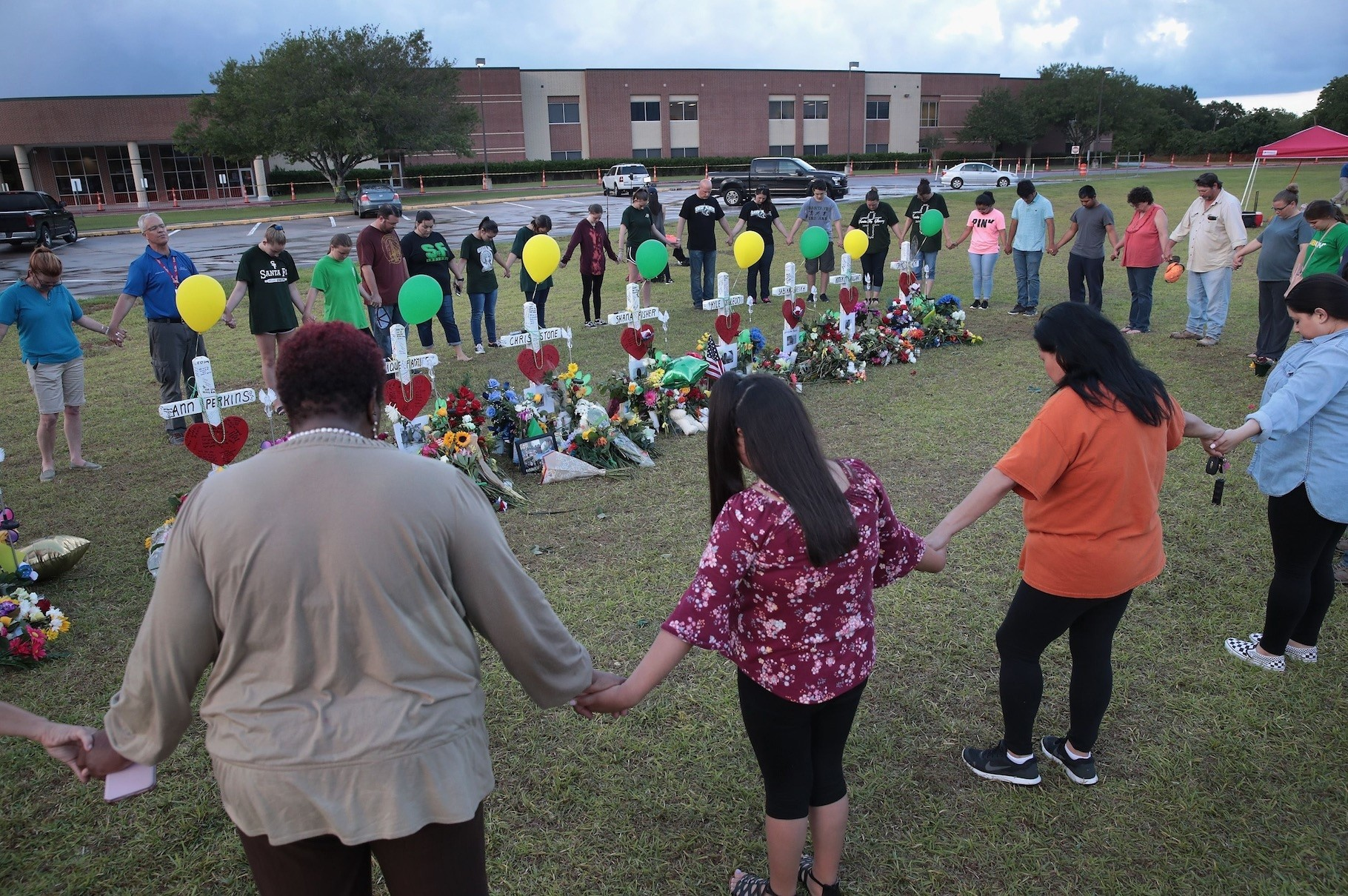 Mourners pray around a memorial in front of Santa Fe High School, Texas, May 21.