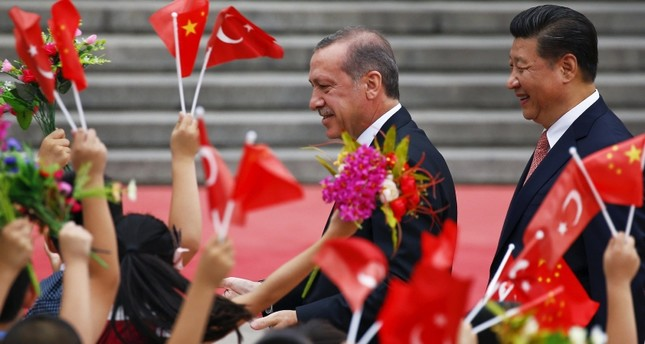 President Recep Tayyip Erdoğan (L) and his Chinese counterpart Xi Jinping greet children waving their country's national flags during a welcoming ceremony outside the Great Hall of the People in Beijing July 29, 2015. (Reuters Photo)