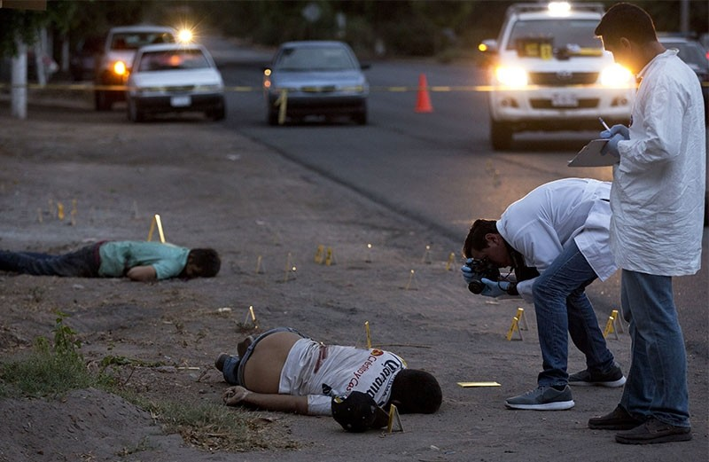 Investigators take pictures at the crime scene next to bodies lying on a road. 59 AK type and AR-15 bullet casings were found in the area. (AP Photo)