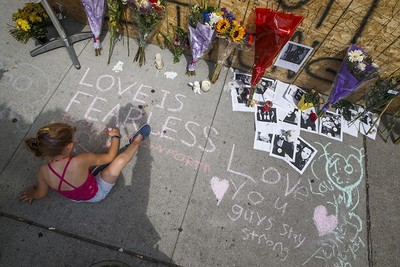 A young girl writes a message on the sidewalk at a site remembering the victims of a Sunday evening shooting on Danforth Avenue, in Toronto on Monday, July 24, 2018. (AP Photo)
