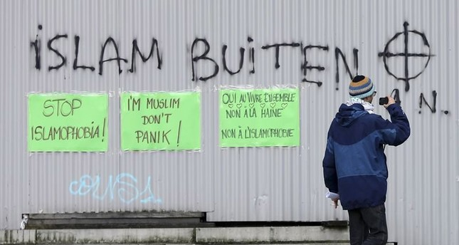 Pasted signs reading Stop Islamophobia and I'm Muslim don't panic are seen under an anti-Islam graffiti during a protest against Islamophobia in front of the Brussels' Justice Palace October 26, 2014. (Reuters Photo)