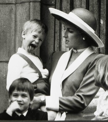 Princess Diana holds Prince Harry as her older son Prince William (L) looks out over the balcony of Buckingham Palace in London, June 11, 1988.