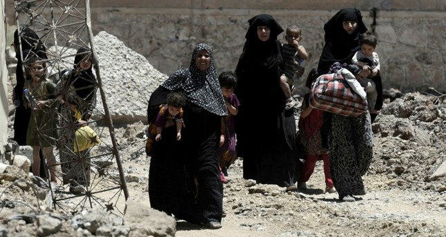 Displaced Iraqi women walk towards Iraq forces as they flee their homes in Mosul's western Al-Shifa district on June 15.