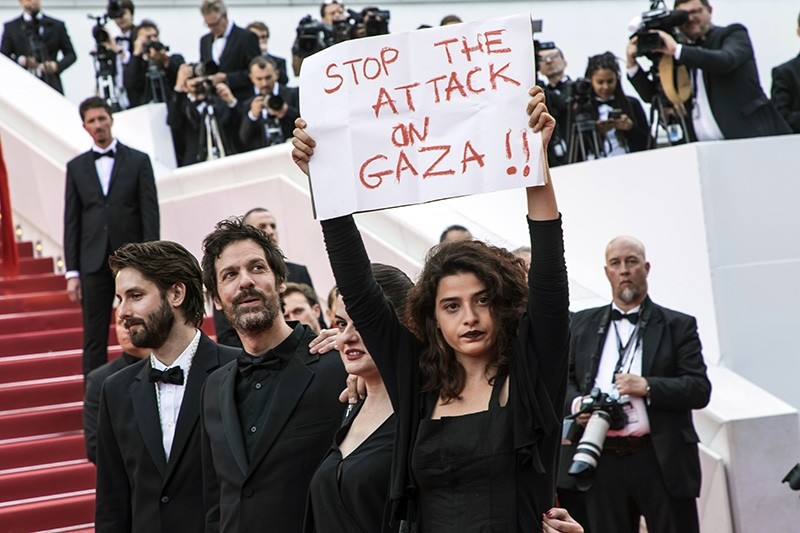 Lebanese actress Manal Issa, from ,My Favorite Fabric,, right, holds a sign that reads ,Stop the Attack on Gaza, at the premiere of the film ,Solo: A Star Wars Story, at the 71st international film festival, Cannes, France, May 15, 2018. (AP Photo)