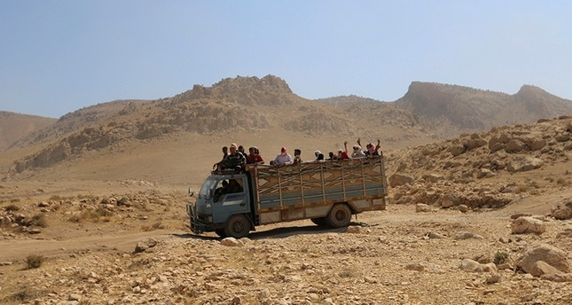 Displaced people from the Yazidi religious minority, fleeing violence from forces loyal to Daesh in Sinjar town, ride on a truck as they are evacuated from Mount Sinjar in northern Iraq, August 2014 (Reuters File Photo)