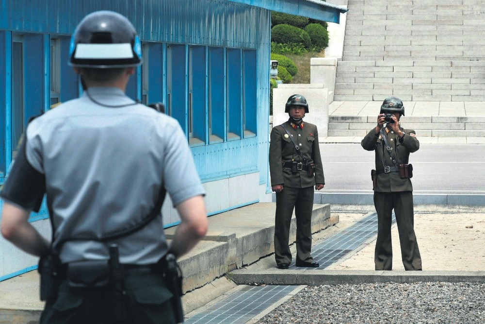 A North Korean soldier takes a photo of a South Korean soldier on guard just behind the military demarcation line that traverses the inter-Korean truce village of Panmunjom.