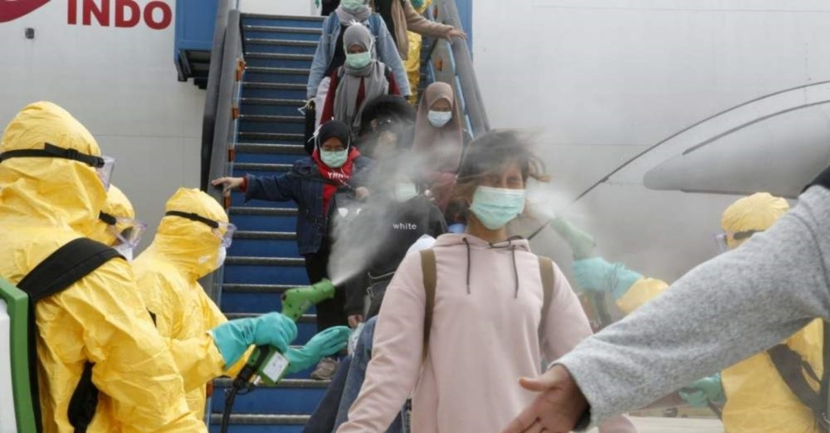 Medical officers spray Indonesian nationals with antiseptic after they arrive from Wuhan at Hang Nadim Airport Batam, Feb. 2, 2020. (Reuters Photo)