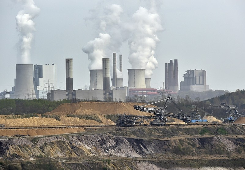 In this April 3, 2014 file photo giant machines dig for brown coal at the open-cast mining Garzweiler in front of a smoking power plant near the city of Grevenbroich in western Germany. (AP Photo)
