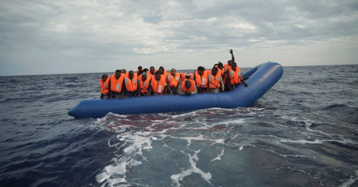 A migrant waves his hand in the air from on a blue rubber boat some 14 nautical miles from the coast of Libya in Mediterranean Sea, Sunday, Sept. 8, 2019. (AP Photo)