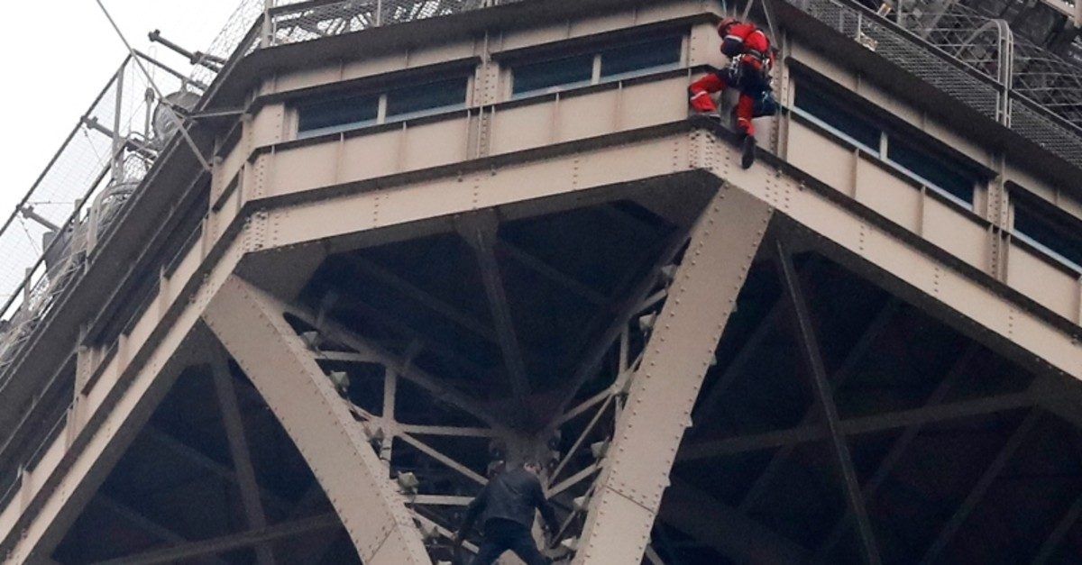 A rescue worker, top in red, hangs from the Eiffel Tower while a climber is seen below him between two iron columns Monday, May 20, 2019 in Paris. (AP Photo)