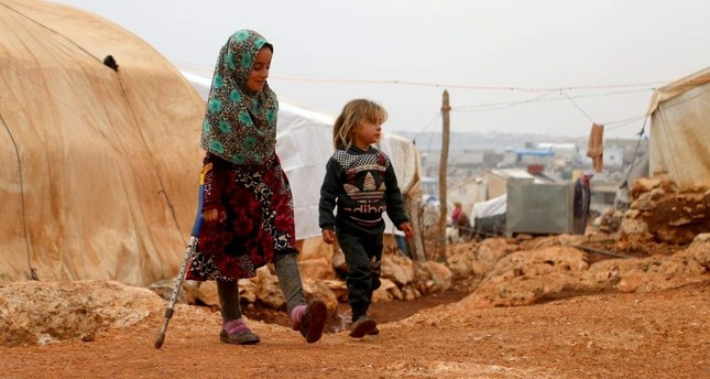 9-year-old Syrian girl Maya Meri seen walking in a refugee camp in Syria thanks to prosthetic legs she received in Turkey last year. AA Photo