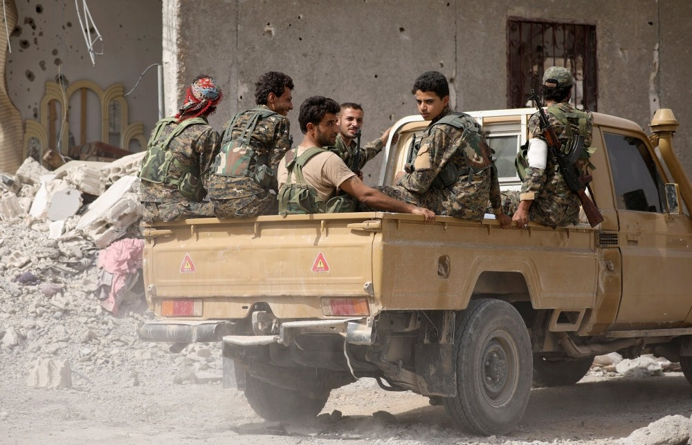 Syrian Democratic Forces (SDF) members sit on the back of a pick-up truck in Raqqa, Syria Sept, 25, 2017.