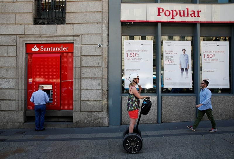 A man uses a cash dispenser at a branch of Spain's biggest bank Santander next to a Banco Popular branch in Madrid, Spain, June 7, 2017. (Reuters Photo)
