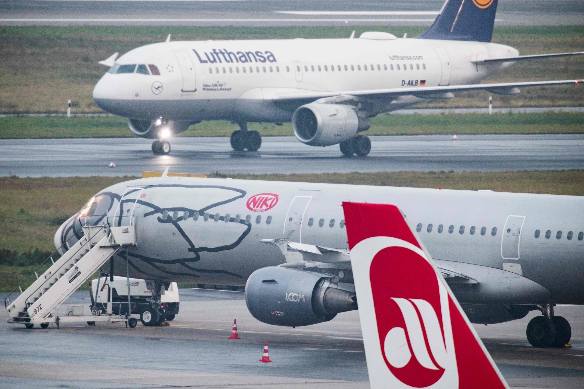 An airplane of German airline Lufthansa (background) rolls past planes of the airlines Niki (C) and Air Berlin (foreground) at the airport in Duesseldorf, western Germany, on December 1, 2017. (AFP Photo)