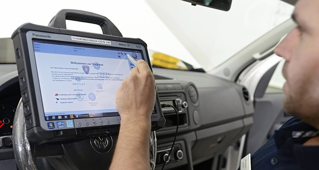 Chief mechanic Ueli Portmann loads a software update into a EA189 diesel engine of a Volkswagen (VW) Amarok car after recalling many vehicles following the VW exhaust emissions scandal (EPA File Photo)