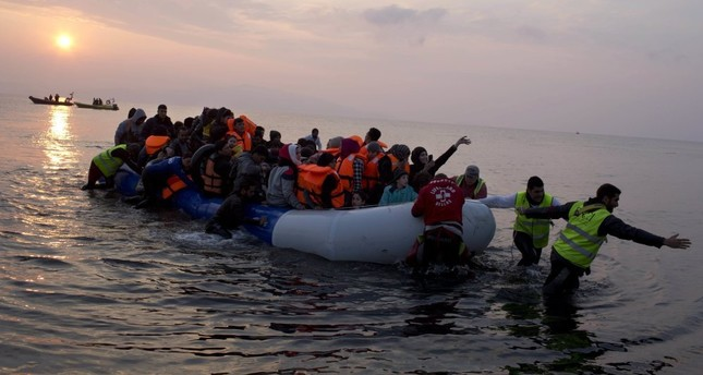 Volunteers help migrants as they arrive at the shore of the northeastern Greek island of Lesbos on March 20.