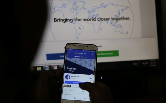 An illustration photo shows the Facebook page displayed on a mobile phone internet browser held in front of a computer screen at a cyber-cafe in downtown Nairobi, Kenya April 18, 2019. (Reuters Photo)