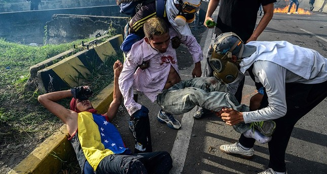 Opposition demonstrators help two injured fellow demonstrators during clashes with riot police on May 31, 2017. (AFP Photo)