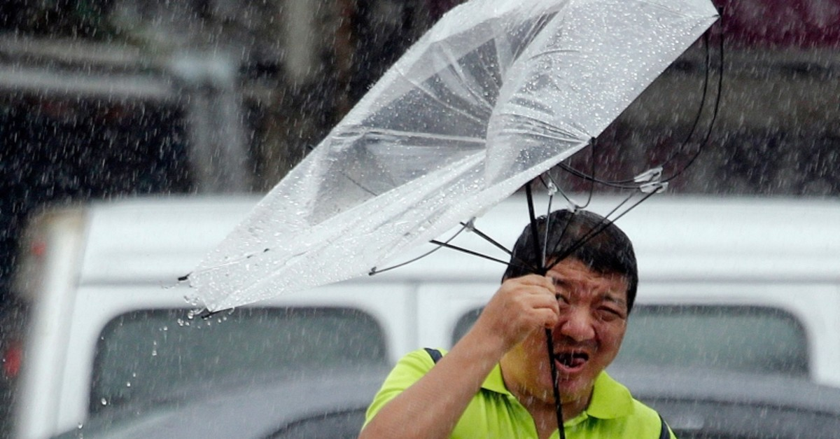 A Taiwanese man holds an umbrella against powerful gusts of wind generated by typhoon Lekima in Taipei, Taiwan, Friday, Aug. 9, 2019. (AP Photo)