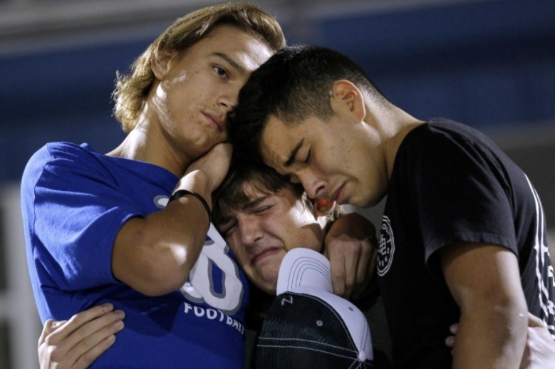 Daniel Friesenhahn (C) is comforted by Derrick Barnhardt (R) and Chris Johnson during a vigil in the memory of those killed in the shooting at the First Baptist Church of Sutherland Springs in La Vernia, Texas, U.S., November 7, 2017. (Reuters Photo)