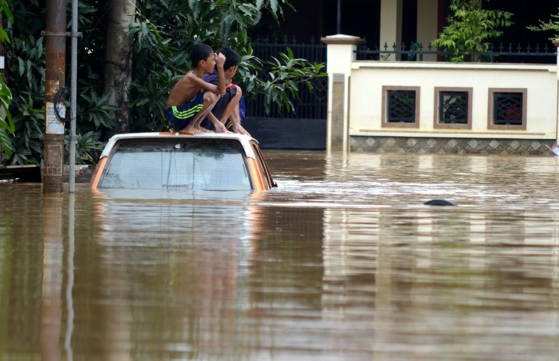 Boys sit on a car at a residential area following floods in Makassar, South Sulawesi, Indonesia, January 24, 2019 in this photo taken by Antara Foto. Picture taken January 24, 2019. (Antara Foto/Sahrul Manda Tikupadang via Reuters)