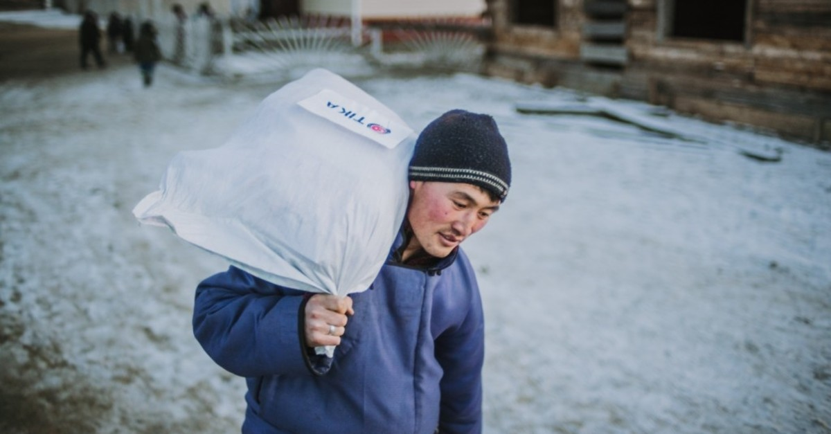 A member of the Dukha community carries an aid package donated by Tu0130KA in Tsaganur, Mongolia, March 2019.