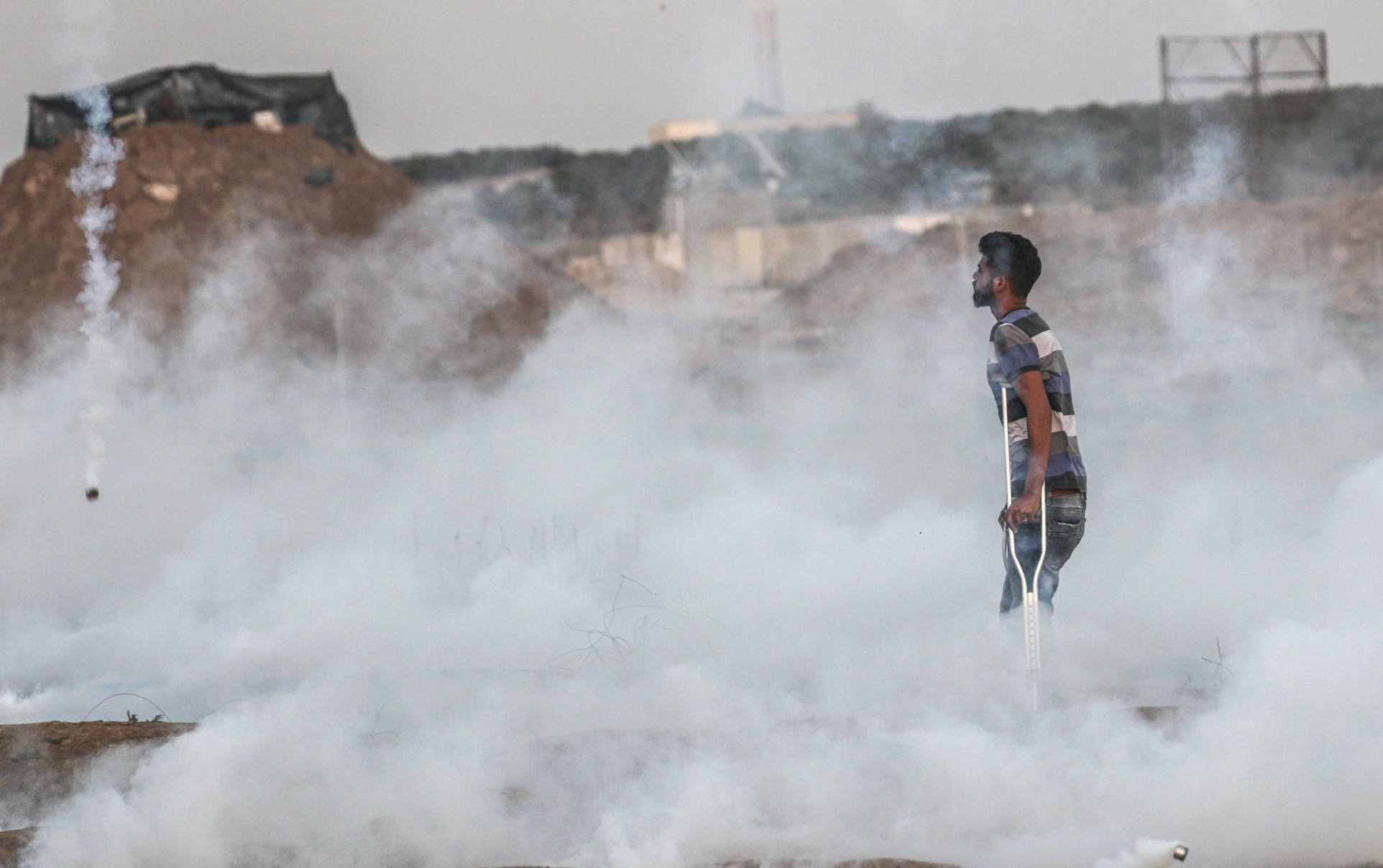 A disabled Palestinian stahds amid Israeli tear gas near the demarcation line between Gaza and Israel on 18 May 2018. 62 unarmed Palestinians were killed by the Israeli security forces during peaceful protests.