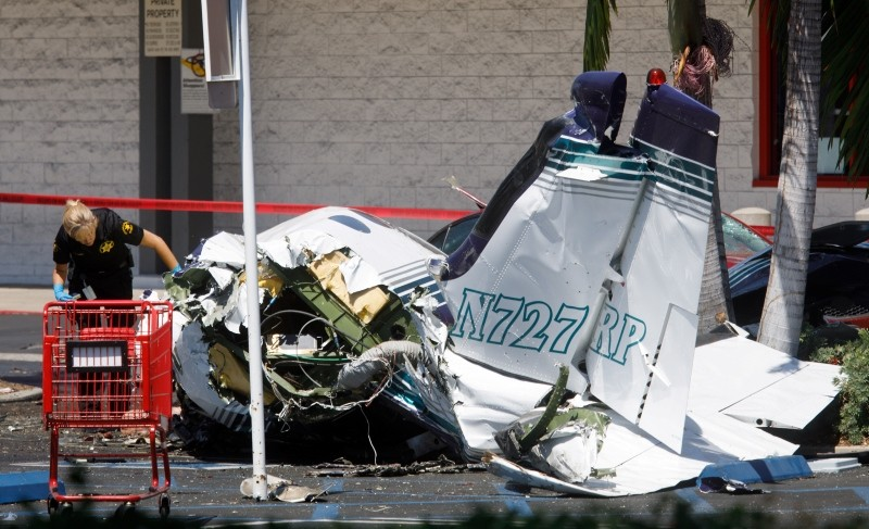 An investigator looks over the wreckage of a small plane that crashed into a strip mall parking lot in Santa Ana, California, USA, 05 August 2018. (EPA Photo)