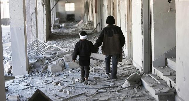 طفلان سوريان يمشيان في أحد أزقة الغوطة المدمرة (AP)
