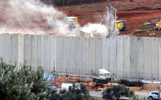 Israeli machinery operates behind the Israel-Lebanon border wall, Dec. 4.