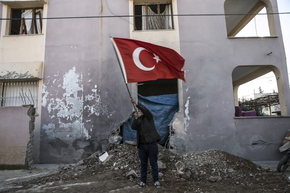 An elderly man waves a Turkish flag in front of a building that was damaged in one of the many PKK/YPG attacks in the region.