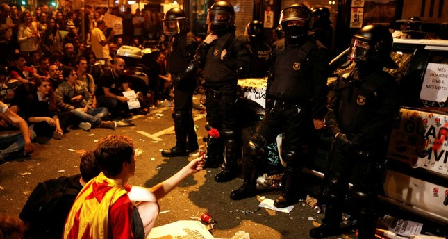 Officers of the Civil Guard stand next to their patrol car, which was damaged by protesters outside the Catalan region's Economy Ministry in Barcelona, Sept. 21.