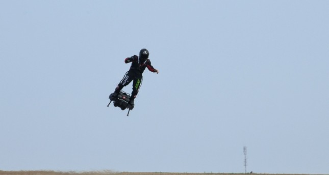 Zapata CEO Franky Zapata flies over fields on his jet-powered hoverboard or Flyboard during a test flight in Saint-Inglevert, northern France, on July 24, 2019 (AFP Photo)