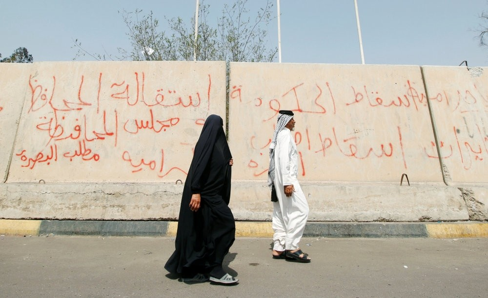 People pass near graffiti painted by protesters after a week of violent protests, Basra, Sept. 9.