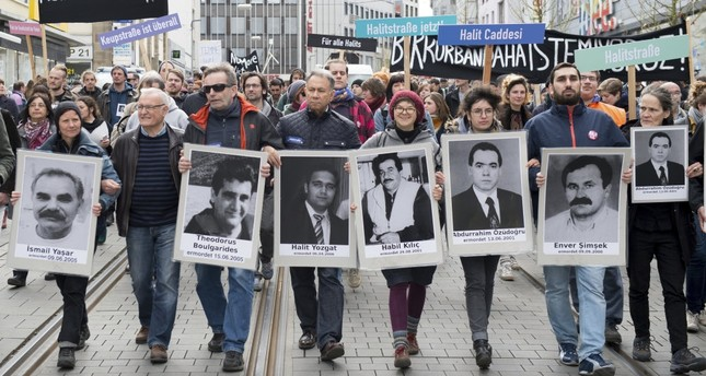 Demonstrators carrying photos of NSU victims and a banner reading No Other Victim! walk through downtown Kassel, Germany on April 6, 2017.