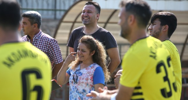 Mukhtar Yonca Kalınlı (middle) talks to the players during a neighborhood football team practice.