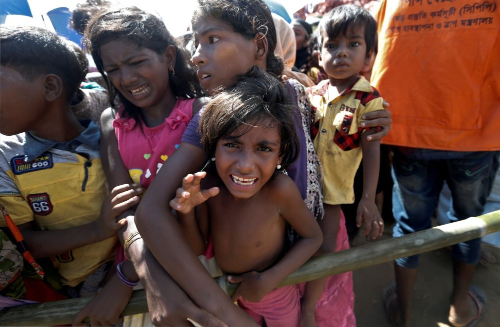 A Rohingya refugee girl reacts as people wait to receive aid in Cox's Bazar, Bangladesh.