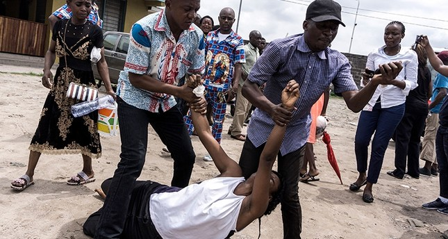 A relative, carried by two men, reacts and mourns the death of a man who succumbed to a gun shot wound during a protest called on by the Catholic Church, to push for the President of the DR of the Congo, to step down on Feb. 25, 2018. (AFP Photo)