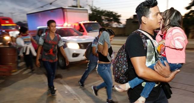 U.S.-bound migrants walk along the roadside as they leave San Pedro Sula, Honduras, at dawn Tuesday, Jan. 15, 2019 (AP Photo)