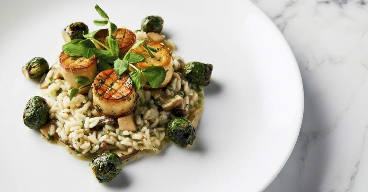 This image released by the Golden Globe Awards shows a dish of king oyster mushroom scallops on a bed of wild mushroom risotto with roasted Brussels sprouts, prepared by Beverly Hilton Executive Chef Matthew Morgan. (Golden Globe Awards via AP)