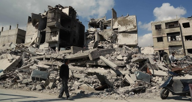 A Syrian man walks past buildings destroyed earlier in regime air strikes in the besieged opposition-held town of Douma in the Eastern Ghouta region on the outskirts of the capital, Damascus, Feb. 28.