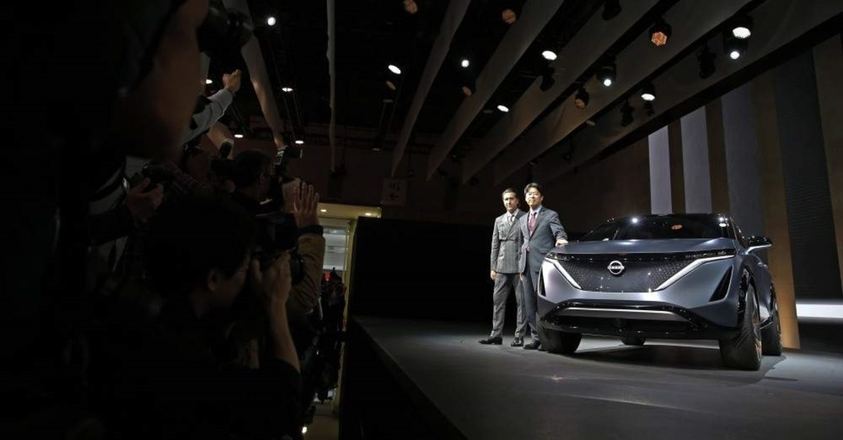 Alfonso Albaisa, left, senior vice president for Global Design for Nissan Motor Corp., and Kunio Nakaguro, executive vice president, pose for photos during Nissan's presentation of the media preview of the Tokyo Motor Show, Oct. 23, 2019, in Tokyo. (AP Photo)