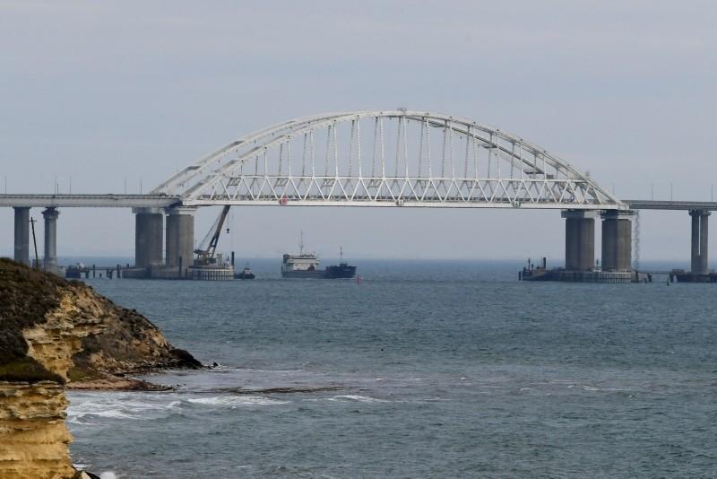 A ship makes way near to the Kerch Bridge, in background, near Kerch, Crimea, Monday, Nov. 26, 2018. (AP Photo)