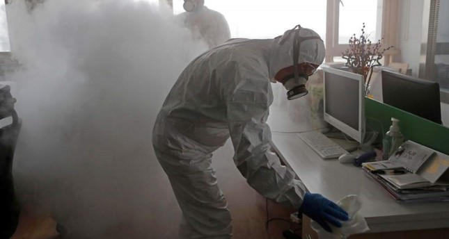 Workers with sanitizing equipment disinfect an office following an outbreak of the coronavirus, Shanghai, Feb. 12, 2020. REUTERS Photo