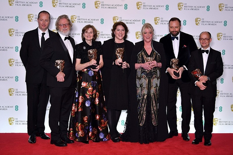 Filmmaker Yorgos Lanthimos (2R) and producers Ceci Dempsey (3R), Ed Guiney (R), Lee Magiday (C), Deborah Davis (3L), Tony McNamara (2L) and Andrew Lowe (L) pose with their awards for an Outstanding British Film for 'The Favourite.' (AFP Photo)